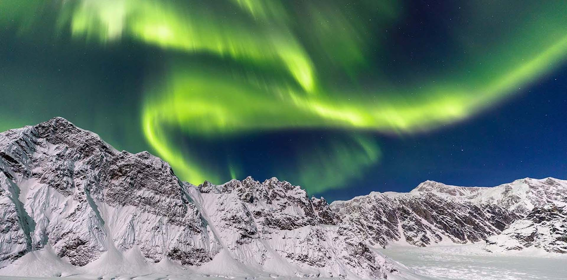northern lights over snowcapped mountain rage