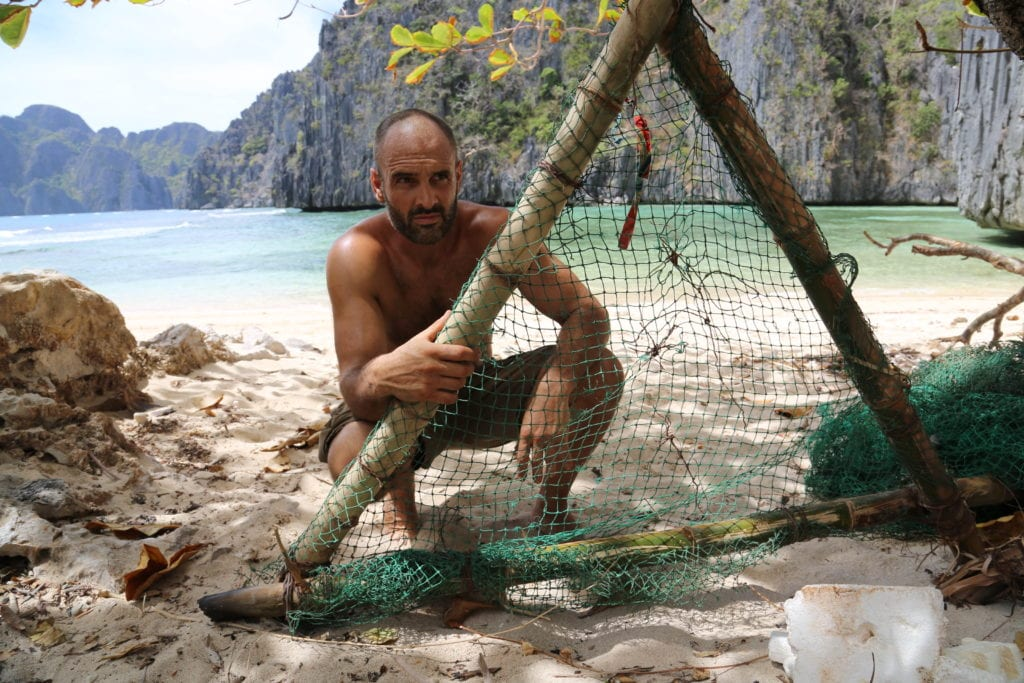 Ed Stafford tying a fishing net to a bamboo frame