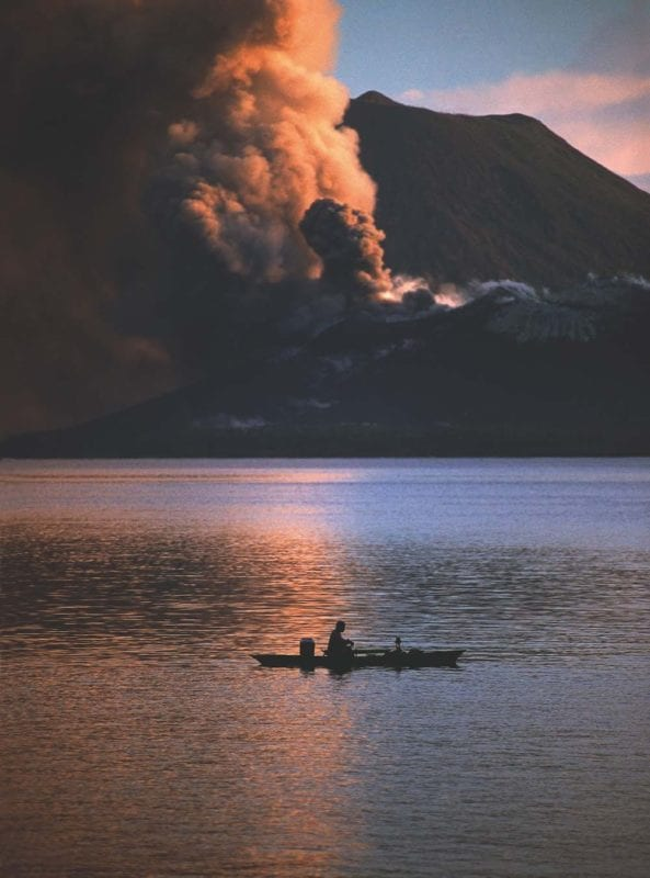 peaceful yet dramatic scene of man in his boat in the foreground and bellowing smoke in the background