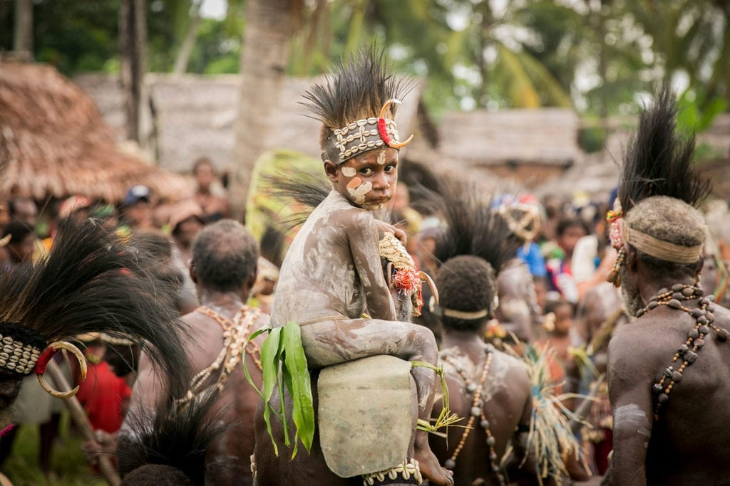 a child sitting on someones shoulders at a tribal celebration