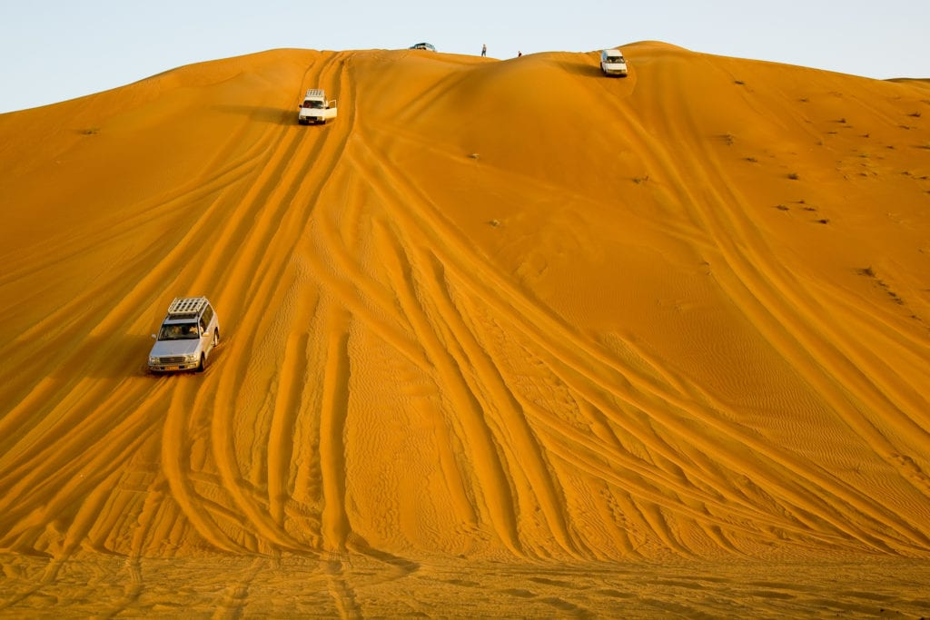 vehicles driving down steep dunes