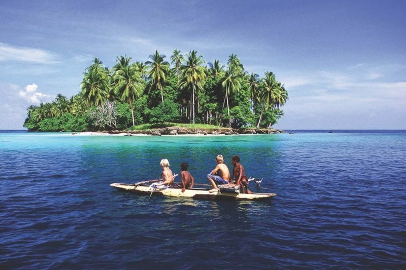 children paddle out on a locally built boat to a desert island