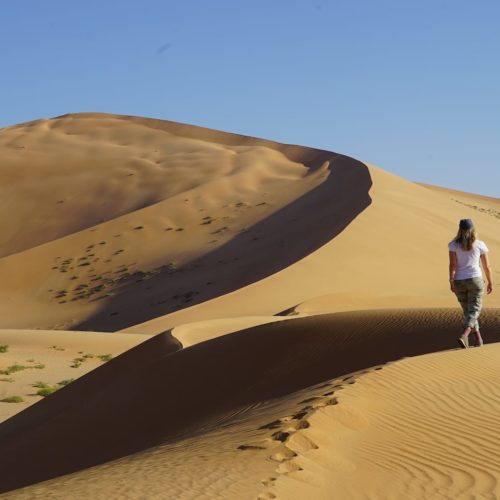 woman walks along dune ridge