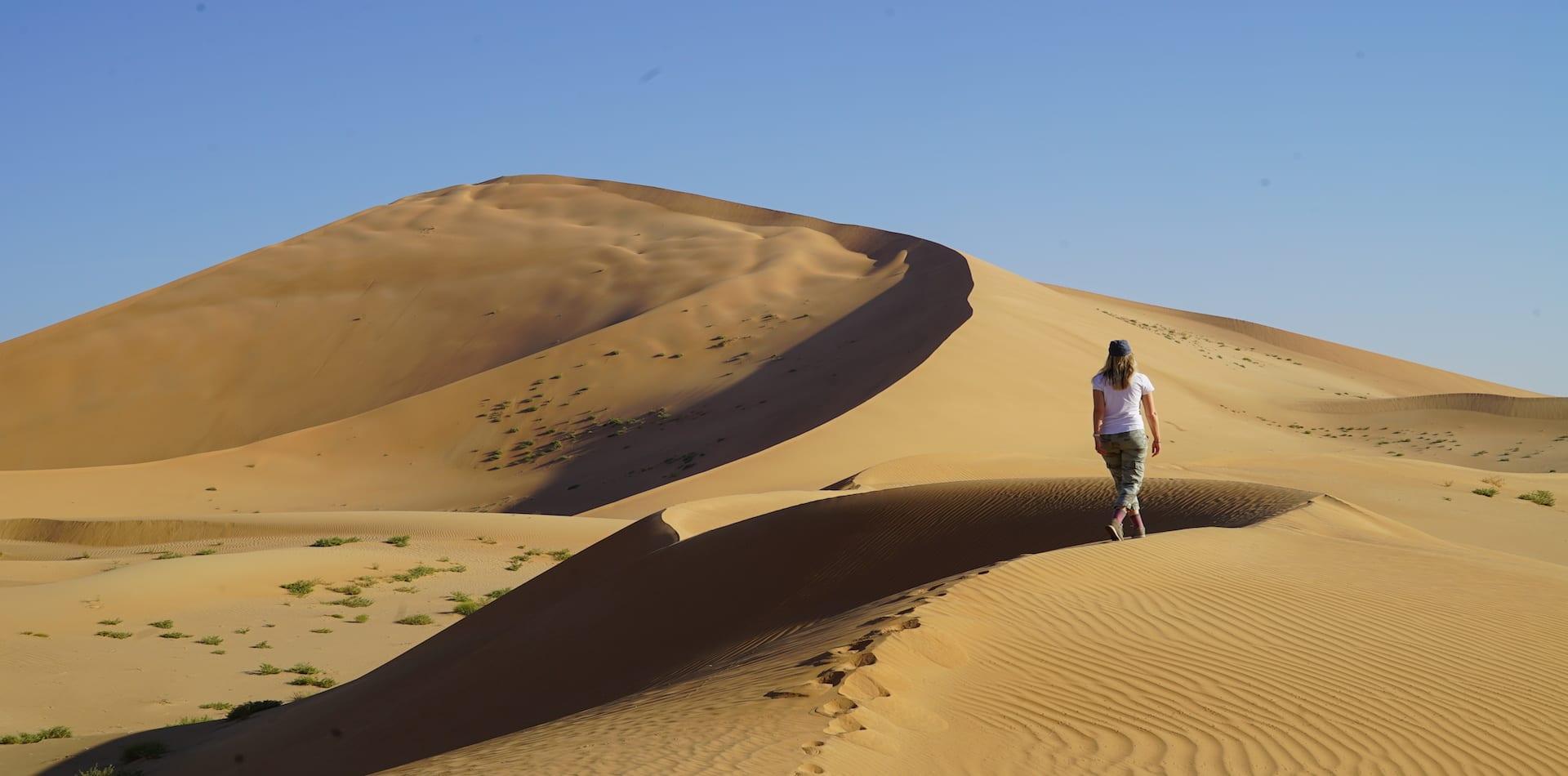 woman walks along dune ridge