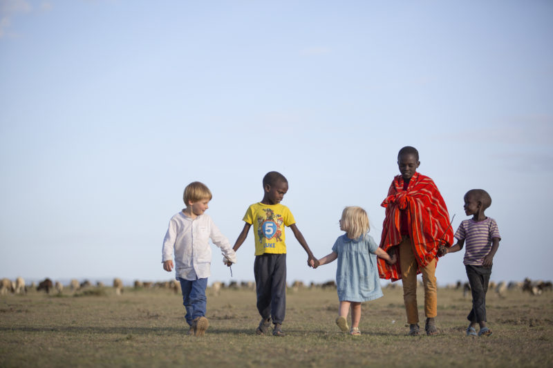 Children holding hands with local children at the Maa Trust, just north of the Maasai Mara National Reserve