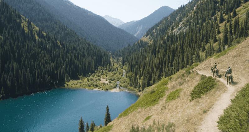 riding a narrow path above a glacial lake