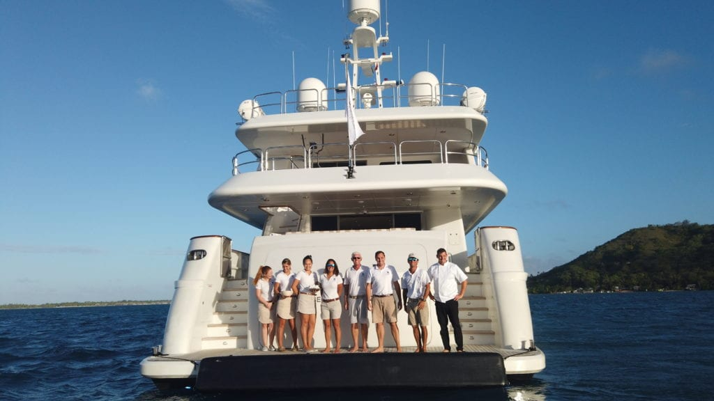Silentworld's crew standing on the stern of the yacht