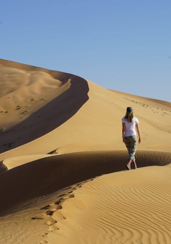 Woman walking in the desert Oman