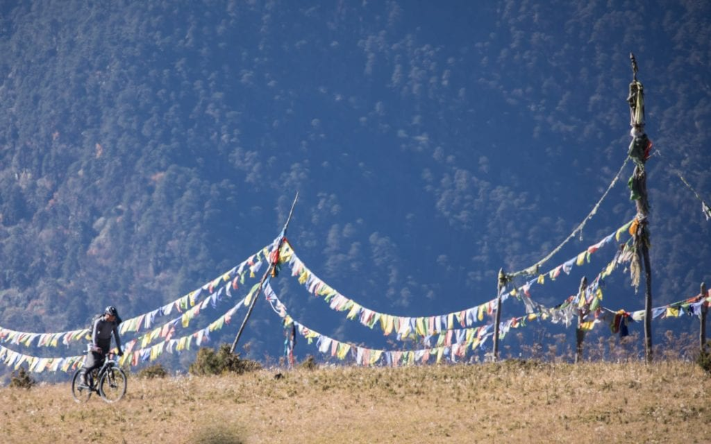 bike ride under prayed flags Bhutan