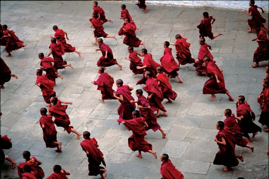 Monks running through courtyard Bhutan