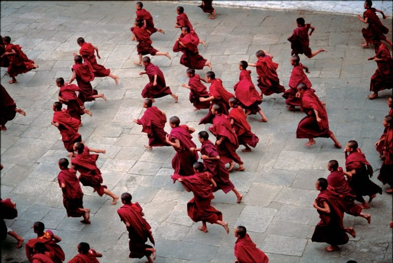 Monks running through courtyard Bhutan