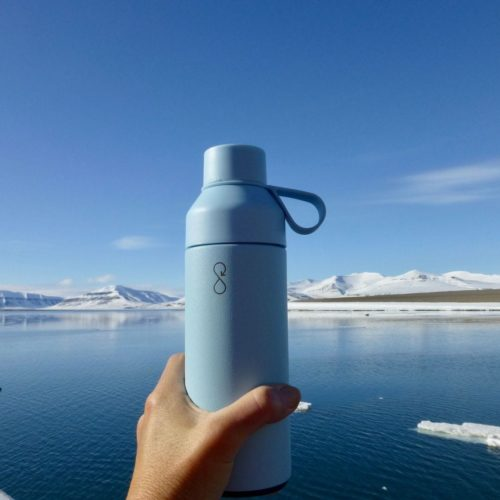 bottle help up against alpine lake and mountainous backdrop