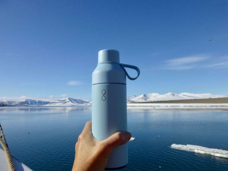 bottle help up against alpine lake and mountainous backdrop