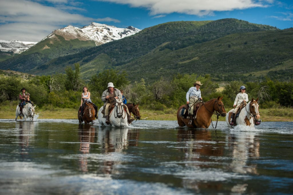 Horse riding through river in Argentina