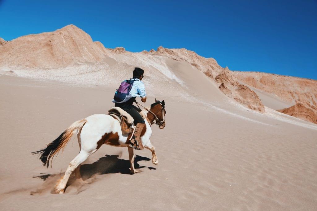 Horseback riding across dunes in Chile