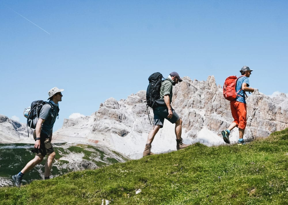 three men hiking in the dolomites during summer