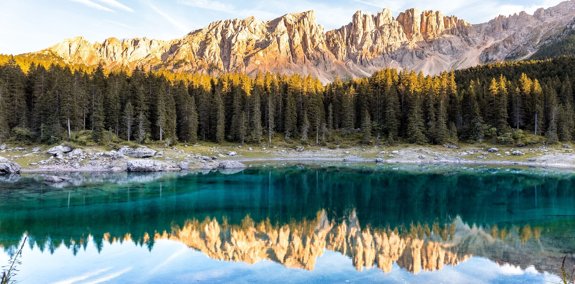 beautiful reflection of the mountains and forest in Lake Carezza, Dolomites