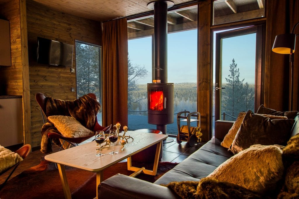 Lounge Area with Fireplace and View at Arctic Treehouse Finland