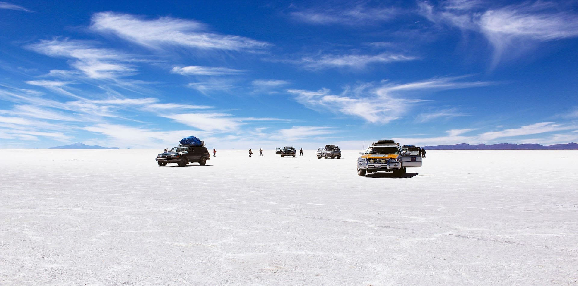 visitors taking in the beauty of the salt lakes where salt flats meets sky