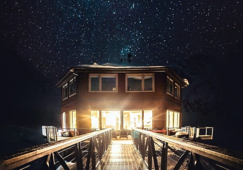 Alaska's Sheldon Chalet under a star scattered sky at night