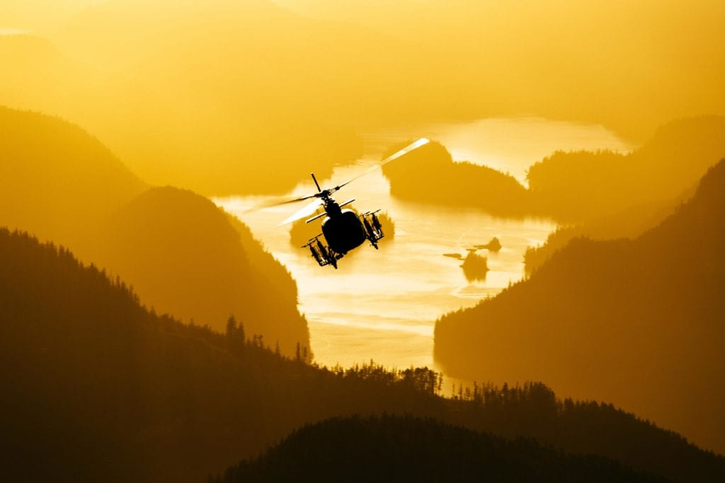 Heli soaring above Nimmo Bay Canada at sunset