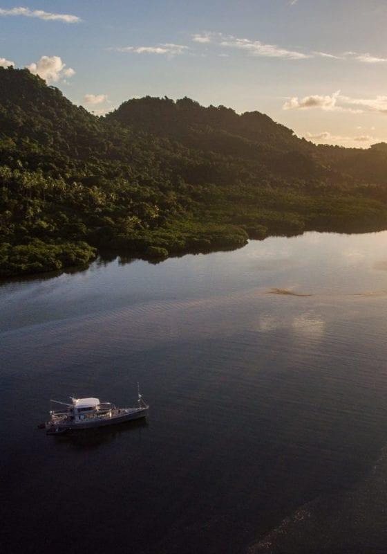 Grey Wolf yacht near hills at sunset