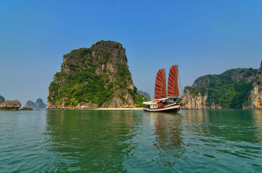 Junk boat with red sails sailing indochina