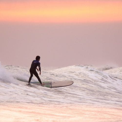 A man surfing at sunset in Hawaii