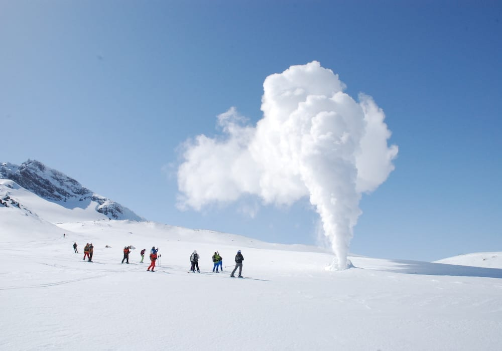 a group standing next to a fuming volcano