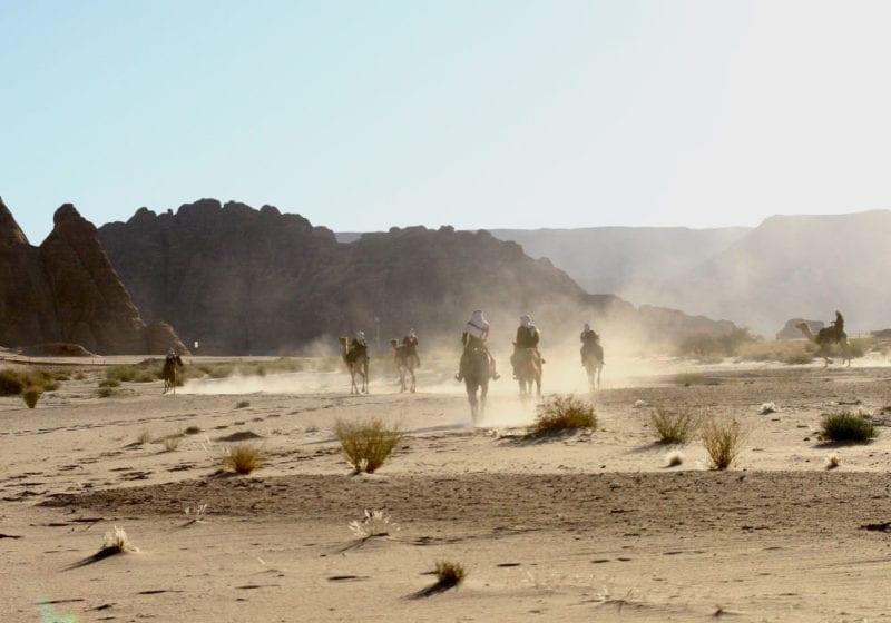 Camel riders in the Saudi desert