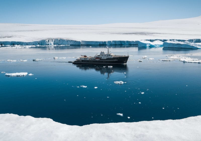 Luxury yacht floating between ice sheets in Antarctica