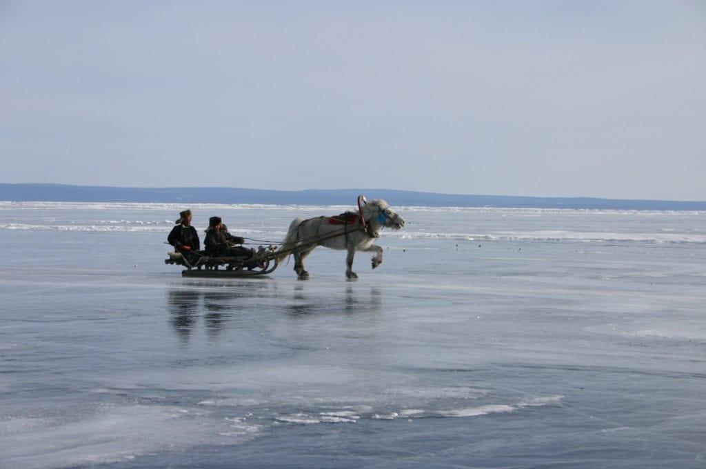Mongolia horse drawn sledge across frozen lake