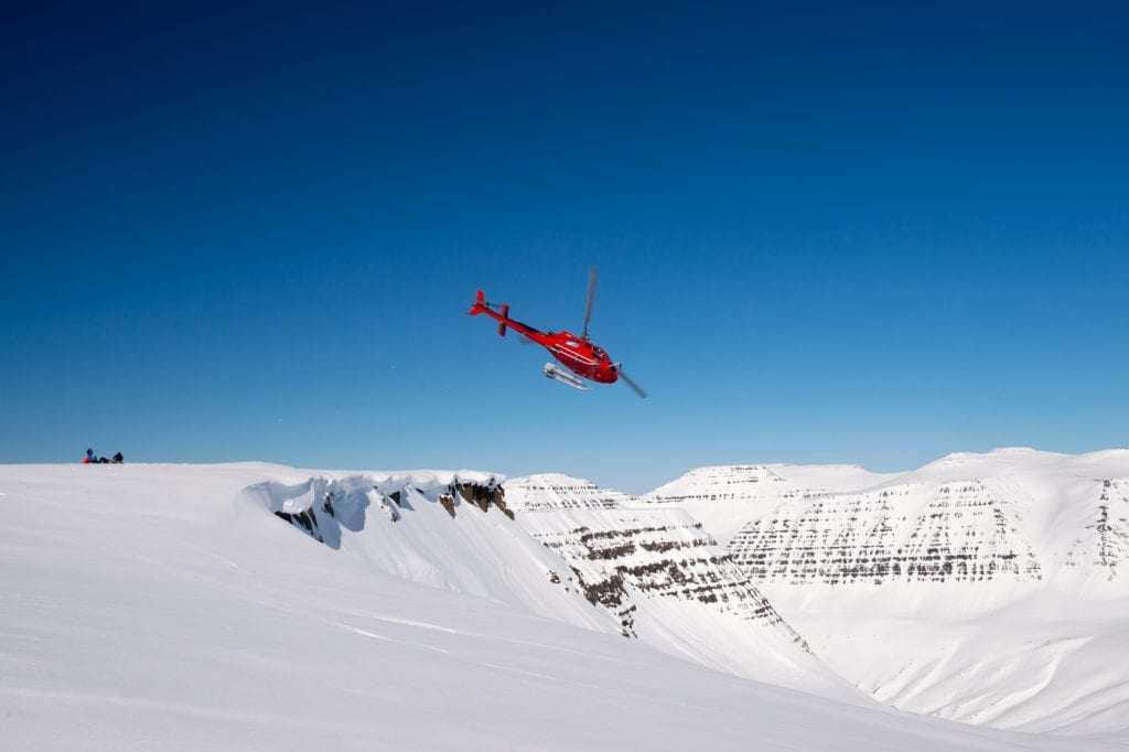 Helicopter Over Snowy Cliffs and Mountains in Iceland
