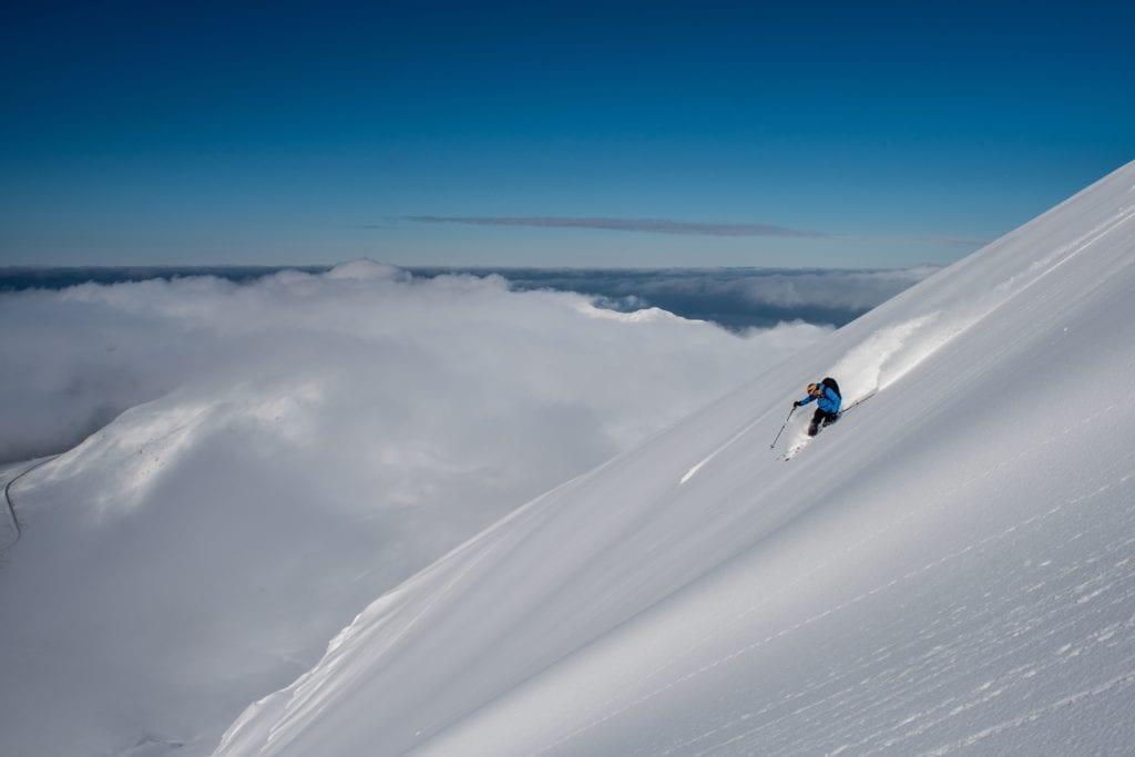 Skiing under a clear blue sky in fresh powder iceland