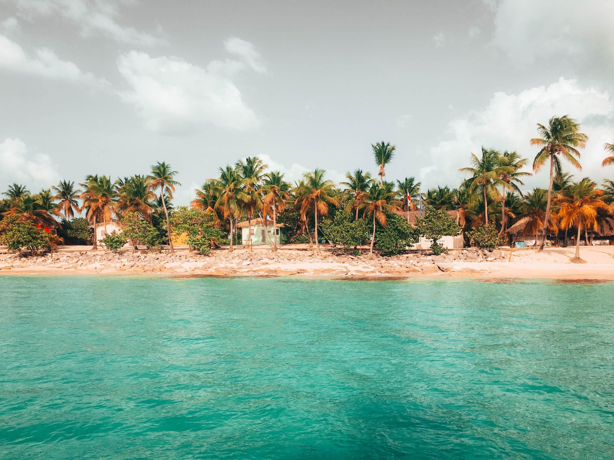 colourful beach shacks on a palm fringed beach