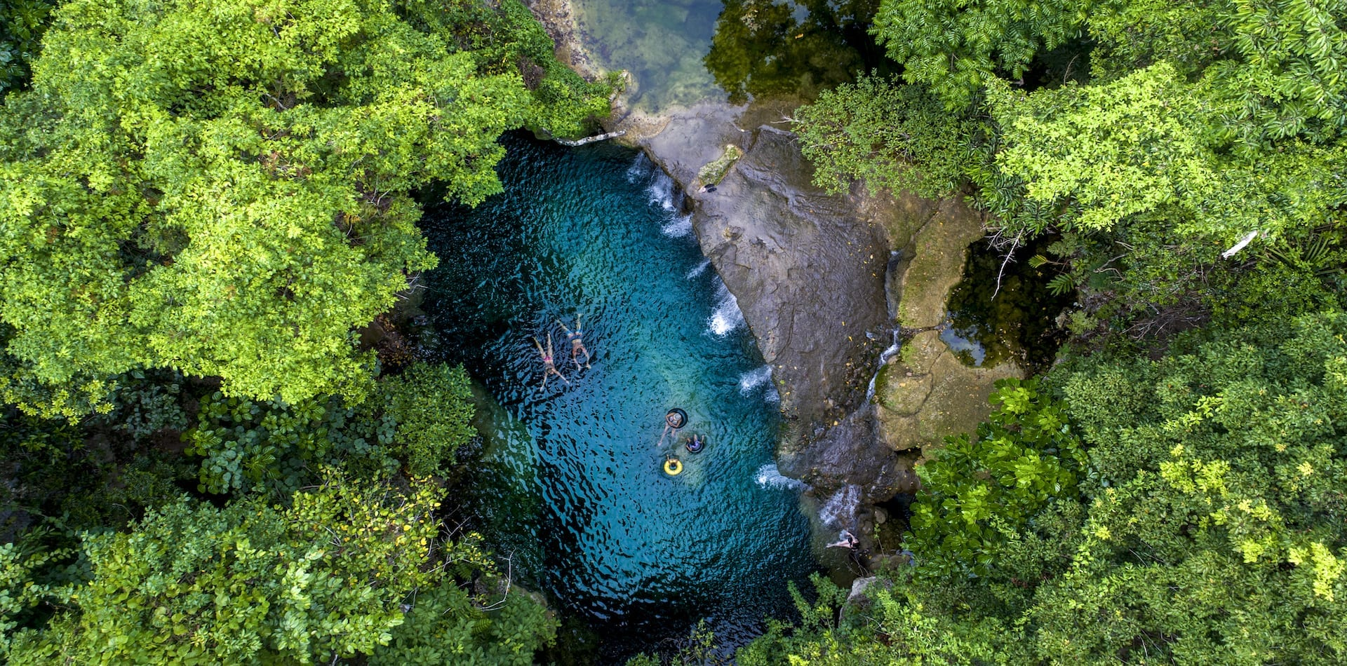 family floating in a pool amongst thick jungle in a remote part of Vanuatu