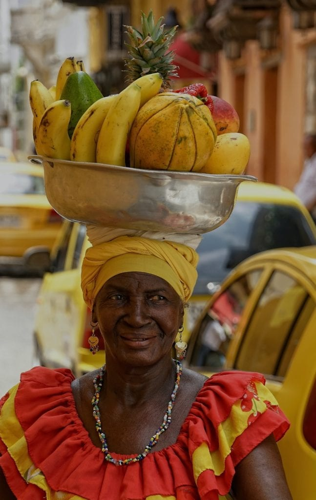 A local woman at market balancing a basket of fruit on her head in Cartagena, Colombia