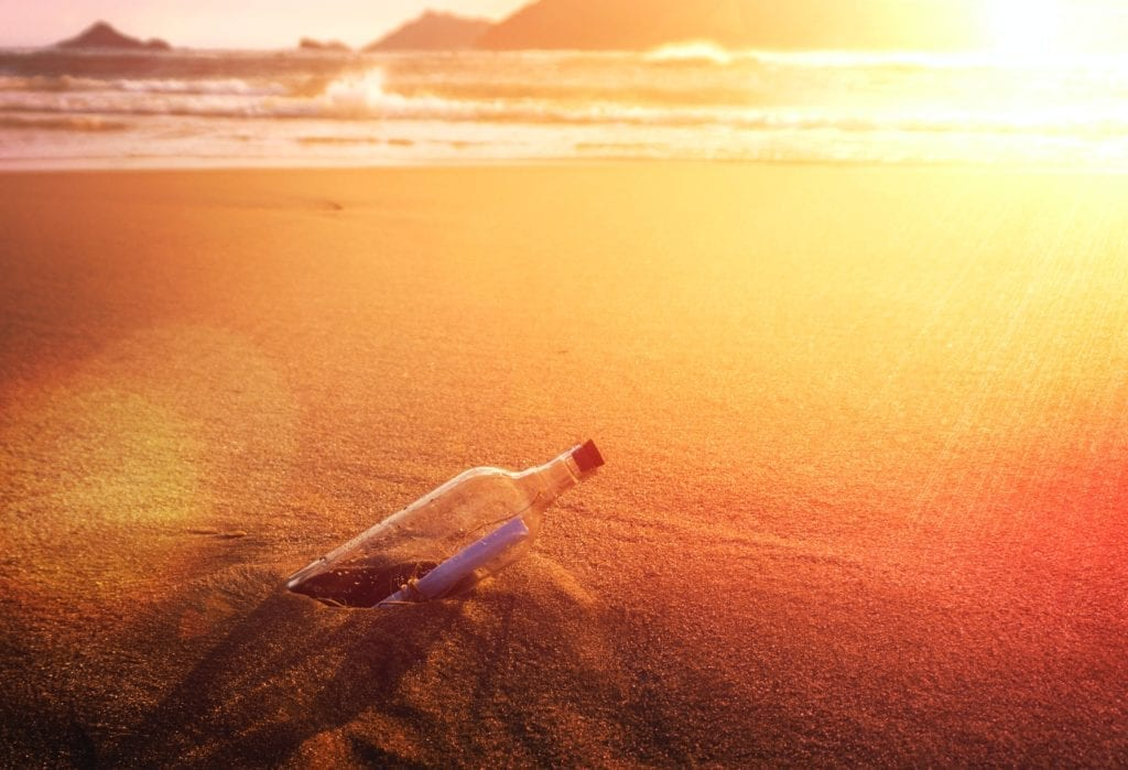 mysterious message in a bottle planted on a beach at sunset