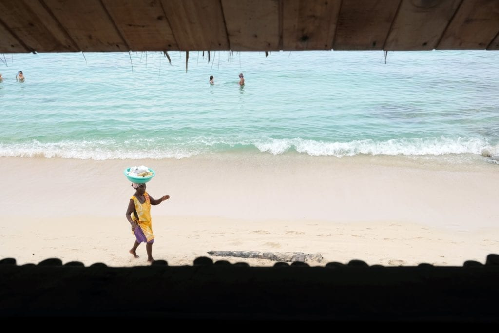 Woman wandering down a beach balancing a basket on her head in Baru, Colombia
