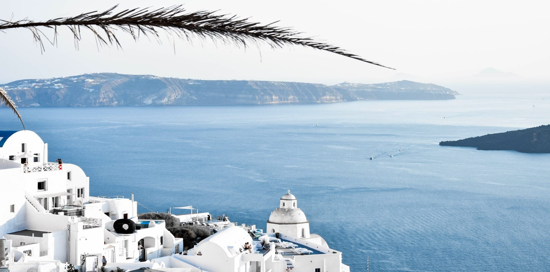 view over whitewashed buildings and pristine Greek ocean landscape