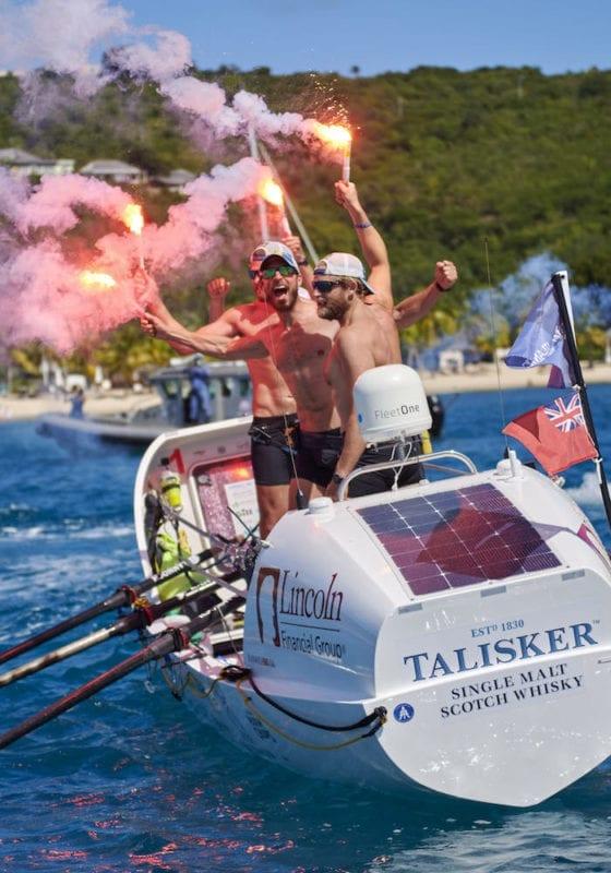 Latitude 35 team celebrating with flares in English Harbour, Antigua