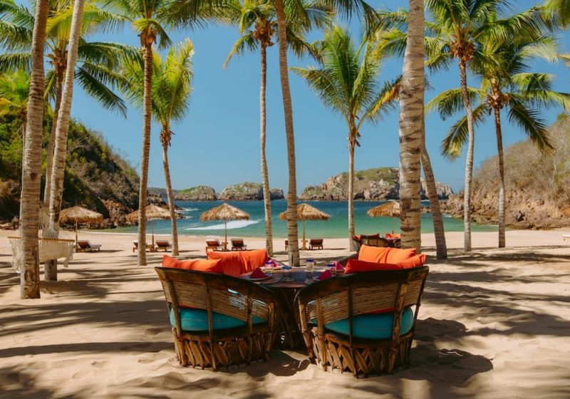 Boho chic beach chairs on a palm tree beach, Cuixmala Mexico