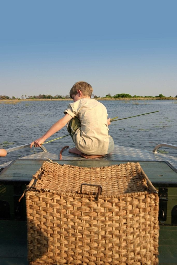 Child on the bow of a river boat in Angola