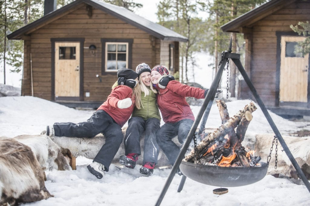 Young children cozied up around a fire in the snow