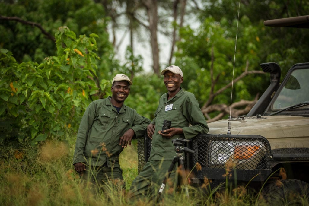 Trained Field Rangers leaning on their jeep in the African bush
