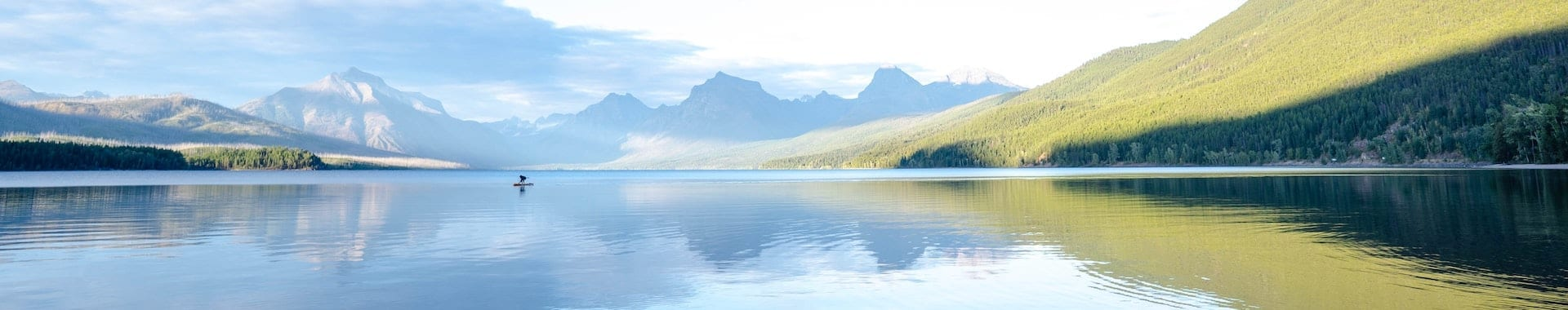 A paddle boarder on a picturesque lake in Montana, USA