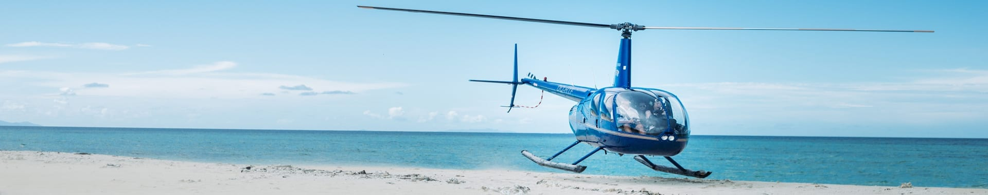 heli landing on a white sandy beach in Fiji