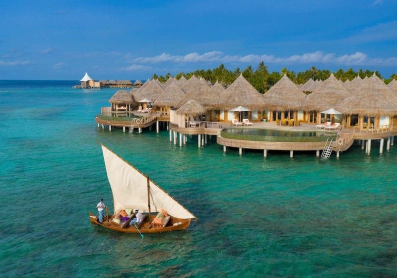 Authentic boat sailing past the exterior of the Nautilus private villas