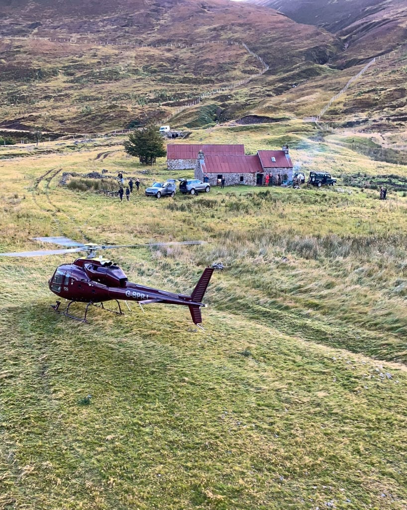 Helicopter and land rovers outside a cottage in the Scottish Highlands, Scotland
