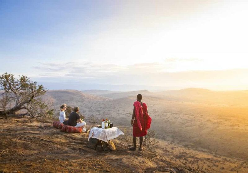 A couple enjoying sundowners at sunset being looked after by a Masai mara tribe member in Kenya, Africa